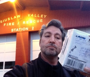 Standing outside of Station 2 with the Package of Mystery (white box)