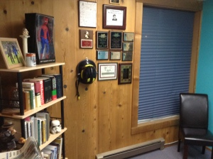 "My reference library of AP Style books, newspaper design, Thesaurus and Origins of Marvel Comics superheroes. Next to it is what I call my ""well-hung"" wall of awards, which have all been in a box for 17 years."
