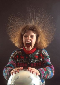 Girl with hair standing on end because of static electricity while touching a vandergraf generator. science, electricity, static, vandergraf generator, hair, girl, surprise, excitement, fear, fun